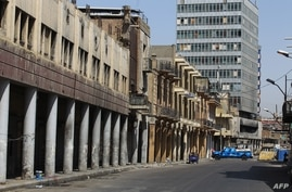 A picture taken on June 11, 2020 shows an empty street in Baghdad and blocked by a police car during a curfew in the Iraqi…