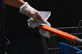 An employee wearing a glove cleans shopping carts at Walmart, July 22, 2020 in Burbank, California. - The country's most…