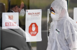 A medical worker enters the Epping Gardens aged care facility in the Melbourne suburb of Epping on July 30, 2020, as the city…