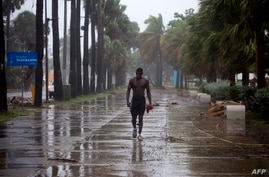 A man walks under pouring rain during Isaias storm in Santo Domingo, on July 30, 2020. (Photo by Erika SANTELICES / AFP)