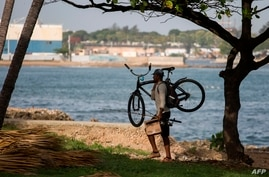 A cyclist walks along the seafront in Santo Domingo on July 29, 2020. - Dominican Republic's Emergency Operation Center (COE)…