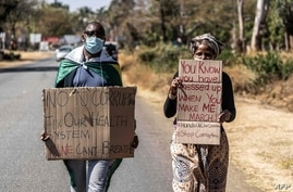 A man and a woman hold placards during an anti-corruption protest march along Borrowdale road, on July 31, 2020 in Harare. -…