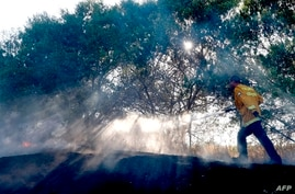 An Israeli fireman extinguishes a fire in a field near the Israel-Gaza border that was reportedly caused by an incendiary…