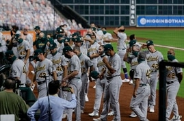 HOUSTON, TEXAS - AUGUST 28: The Oakland Athletics walk off the field before playing the Houston Astros as both teams elected…