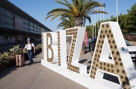 A tourist walks with her suitcase outside the airport in Ibiza on July 30, 2020. - With Spanish health authorities struggling…