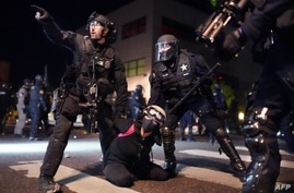 PORTLAND, OR - AUGUST 10: Portland police and Oregon State Patrol officers work together to arrest a protester in front of the…