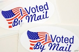 "TOPSHOT - Stickers that read ""I Voted By Mail"" sit on a table waiting to be stuffed into envelopes by absentee ballot election…"
