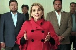 This picture released by hte Bolivian goverment shows the interim president of Bolivia, Jeanine Anez, announcing her withdrawal…