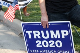 A supporter of US President Donald Trump holds a sign to show their support before the vice presidential debate outside…