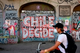 """A man rides a bicycle past a wall a graffiti reading """"Chile decides"""" in Santiago, on October 23, 2020, two days ahead of a…"""