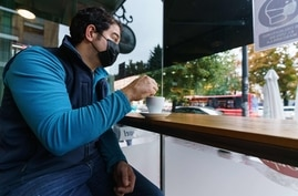 A man wearing a face mask sits at a coffee shop in Burgos, northern Spain, on October 21, 2020, on the first day of a two week…
