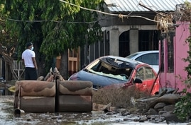 TOPSHOT - A man looks on near a destroyed car and sofas covered in mud after the passage of Hurricane Eta, now downgraded to…