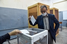 An Algerian man casts his ballot at a polling station in the capital Algiers during a vote for a revised constitution, on…