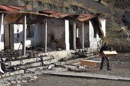 A man carries a table near a destroyed house in the country side outside the town of Kalbajar on November 23, 2020. -…