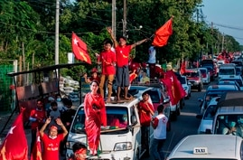 Supporters of the National League for Democracy (NLD) party celebrate with a cut-out figure of Myanmar state counsellor Aung…