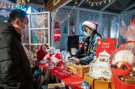 This photo taken on December 24, 2020 shows a vendor offering drinks to a customer at a Christmas-themed market outside of a…