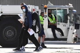 Tennis players and officials disembark from a flight after arriving in Melbourne on January 14, 2021, to quarantine ahead of…