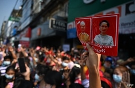 A protester holds up a sign with the images of detained Myanmar civilian leader Aung San Suu Kyi (R) and president Win Myint…