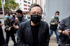 Hong Kong law professor and pro-democracy activist Benny Tai  (C) arrives at Ma On Shan police station in Hong Kong on February…