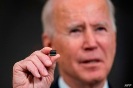 WASHINGTON, DC - FEBRUARY 24: U.S. President Joe Biden holds a semiconductor during his remarks before signing an Executive…