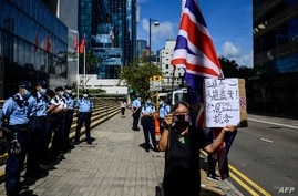 Alexandra Wong (R), an activist known as Grandma Wong, holds a British Union Jack flag outside the District Court in Hong Kong…