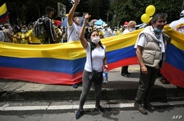People wave the Colombian national flag during a demonstration in opposition to road blockades and violence, after a month of…