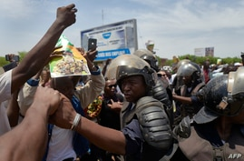 Malian riot police keep supporters away from the vehicle of new President of Mali's transitional government Assimi Goita as he…
