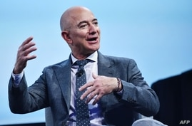 (FILES) In this file photograph taken on October 22, 2019, Blue Origin founder Jeff Bezos speaks after receiving the 2019…