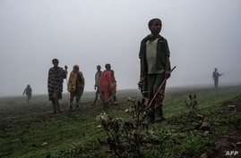TOPSHOT - Children stand amidst fog on the site of a future camp for Eritrean refugees, in a rural area near the village of…