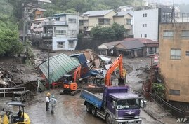 Mangled houses and other debris swept away by a landslide are seen by a road following days of heavy rain in the Izusan area of…