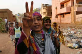 Sudanese protesters flash victory signs and shout slogans, as they march during a protest against the military council, in Khartoum, Sudan, June 27, 2019.