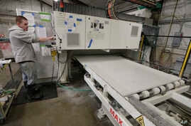 A worker begins production of a kitchen countertop that is being cut from imported quartz slabs from China in the production facility at Marble Uniques in Tipton, Ind., Friday, May 3, 2019.