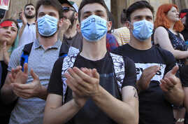 """Young opposition demonstrators wearing masks reading """"Russia Occupant """" gather in front of the Georgian Parliament building in Tbilisi, Georgia,  June 21, 2019."""