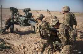 FILE - In this June 10, 2017 photo provided by Operation Resolute Support, U.S. Soldiers with Task Force Iron maneuver an M-777 howitzer, so it can be towed into position at Bost Airfield, Afghanistan.  Reversing his past calls for a speedy exit, U…