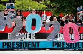 Supporters for Democratic presidential candidate Cory Booker hold signs outside the Iowa Democratic Party's Hall of Fame Celebration, June 9, 2019, in Cedar Rapids, Iowa.