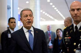 FILE - In this Wednesday, June 26, 2019 file photo, Turkish Defense Minister Hulusi Akar, center left, arrives to NATO headquarters in Brussels. Turkey's defense ministry has said it is ready to retaliate against any attacks on Turkish vessels and…