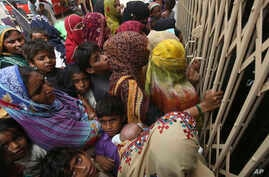 Pakistani villagers wait outside a hospital for blood screening for HIV at a hospital in a village near Ratodero, a small town in southern province of Sindh in Pakistan.