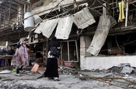 FILE - In this Wednesday, Aug. 1, 2012 file photo, Iraqis inspect the aftermath a day after a car bomb attack in a shopping area in Karradah, Baghdad, Iraq. In his first purported online message on July 21, 2012, al-Qaida in Iraq leader Abu Bakr al…