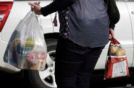 FILE - A shopper leaves a supermarket with goods in plastic bags in Christchurch, New Zealand,  Aug. 10, 2018.