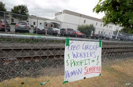 A sign opposing the private contractor that operates the Northwest Detention Center, hangs outside the facility in Tacoma, Wash., July 10, 2018.