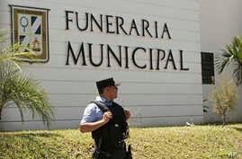 A municipal police officer stands outside the Municipal Funeral Home at La Bermeja Cemetery, where the bodies of Óscar Alberto Martínez Ramírez, 25, and his daughter Valeria, 23 months, arrived in San Salvador, El Salvador, Sunday, June 30, 2019…