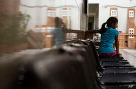 """A Salvadoran migrant girl waits for her food at a migrant shelter in Guatemala City, July 12, 2019. Guatemala's president is to meet Monday in Washington with U.S. counterpart Donald Trump, and officials there have said """"safe third country"""" is on the table, though not a done deal."""