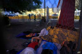 A small group of migrants waiting to seek asylum sleeps at the entrance to the Puerta Mexico international bridge in Matamoros, Tamaulipas state, Mexico, Friday, June 28, 2019. Hundreds of migrants from Central America, South America, the Caribbean…