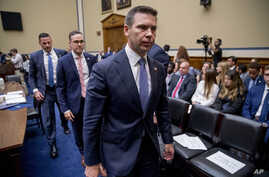 Acting Secretary of Homeland Security Kevin McAleenan, right, departs during a break in testimony before a House Committee on Oversight and Reform hearing on Capitol Hill in Washington, Thursday, July 18, 2019. (AP Photo/Andrew Harnik)