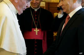 FILE - In this June 10, 2015 file photo, Pope Francis shakes hands with Russian President Vladimir Putin at the end of their private audience at the Vatican.