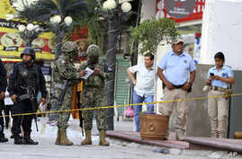 Soldiers from the National Guard, State Police officers of Guerrero and Municipal Police officers of Acapulco guard an area where gunmen killed and wounded multiple people inside a bar in Acapulco, Mexico, Sunday July 21, 2019. (AP Photo/Bernardino…