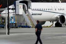 FILE - In this March 14, 2019, file photo, a worker walks next to a Boeing 737 MAX 8 airplane parked at Boeing Field in Seattle. Flyadeal, a Saudi budget carrier says it is ordering 30 new Airbus planes, replacing a $6 billion agreement it had with…