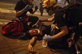 Medical workers help a protester in pain from tear gas fired by policemen on a street in Hong Kong, Sunday, July 21, 2019. Hong Kong police have thrown tear gas canisters at protesters after they refused to disperse. Hundreds of thousands of people…