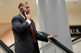 Sen. Lindsey Graham, R-S.C., talks on the phone as he rides the escalator on Capitol Hill in Washington, Wednesday, July 10, 2019, as he heads to a briefing on election security. (AP Photo/Susan Walsh)