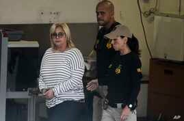 Federal agents escort former Puerto Rico Health Insurance Administration head Ángela Ávila-Marrero who was arrested in San Juan, Puerto Rico, Wednesday, July 10, 2019. Puerto Rico's former secretary of education and four other people including Ávila…